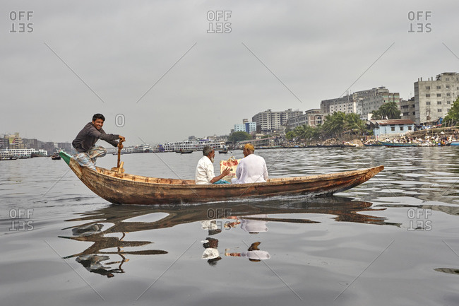 Dhaka, Bangladesh - April 27, 2013: A man navigating his canoe with two passengers on the Buriganga River