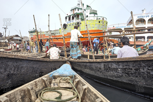 Dhaka, Bangladesh - April 27, 2013: Passengers approaching boats at a small harbor on the Buriganga River