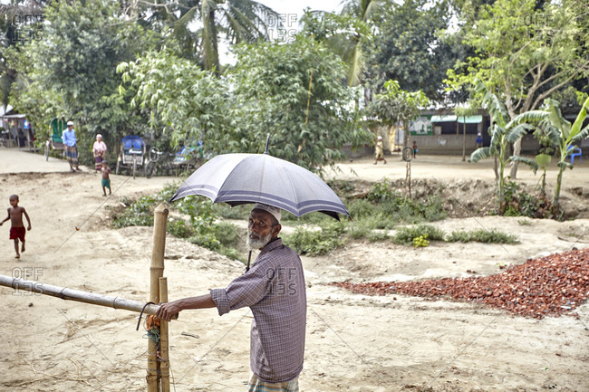 Bangladesh - April 29, 2013: A street portrait of an old man with an umbrella somewhere in rural Bangladesh