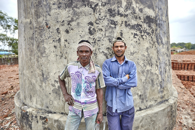Chittagong, Bangladesh - May 2, 2013: Two men posing in front of a chimney at a brick factory