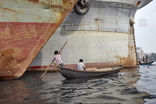 Dhaka, Bangladesh - April 27, 2013: Two males sailing on their boat nearby two huge ships on the Buriganga River