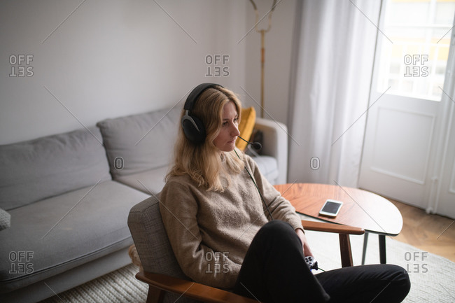 Blonde woman sitting on chair in living room wearing a headset and playing video games