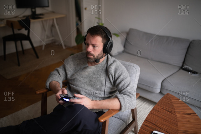 Man sitting on chair in living room wearing a headset and playing video games