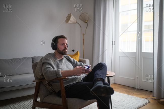 Man relaxing on chair in living room wearing a headset and playing video games