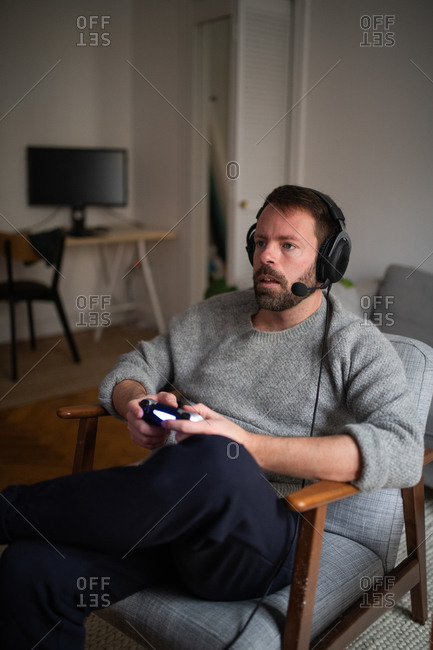 A man relaxing in living room wearing a headset and playing video games