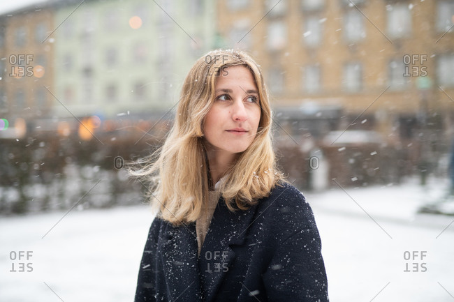 Blonde woman wearing walking on city street during snowfall