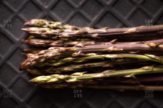 Bunch of wild asparagus on a black slate stone