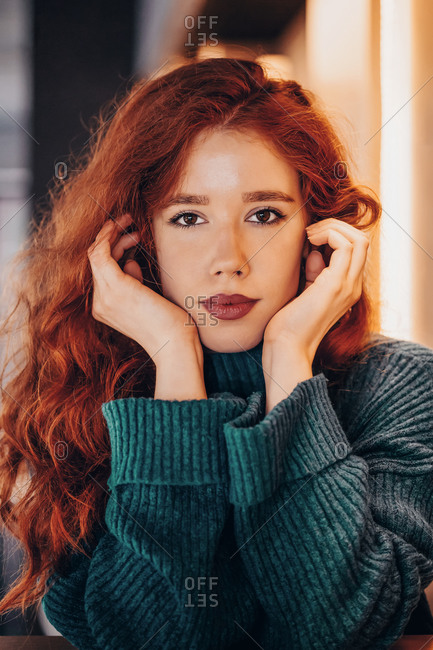 Portrait of an attractive curly haired ginger young woman in a cafe