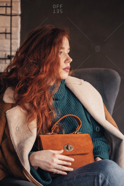 Attractive curly haired ginger young woman posing with a stylish handbag