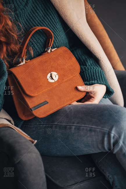Close up of young woman posing with a stylish brown handbag