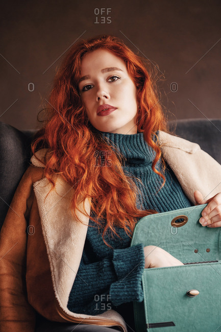 Curly haired ginger young woman posing with a stylish handbag