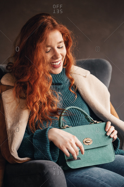 Happy curly haired ginger young woman posing with a stylish handbag