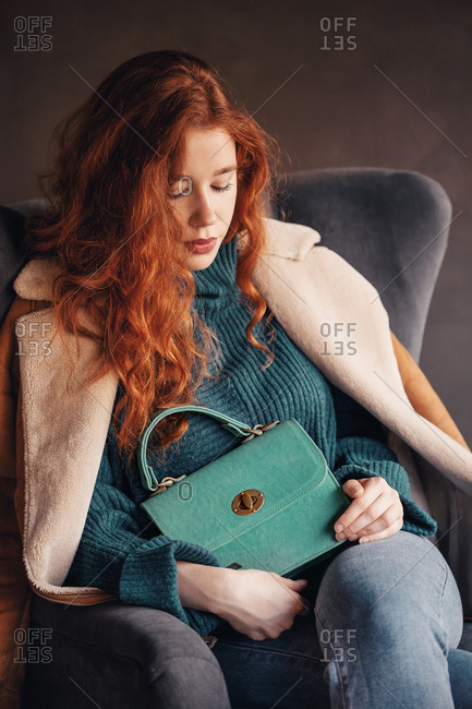 Attractive ginger young woman posing with a stylish handbag