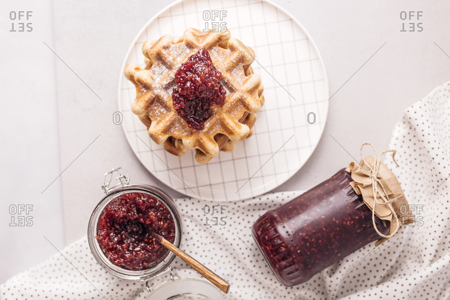 Homemade raspberry jam on the top of waffle on the table