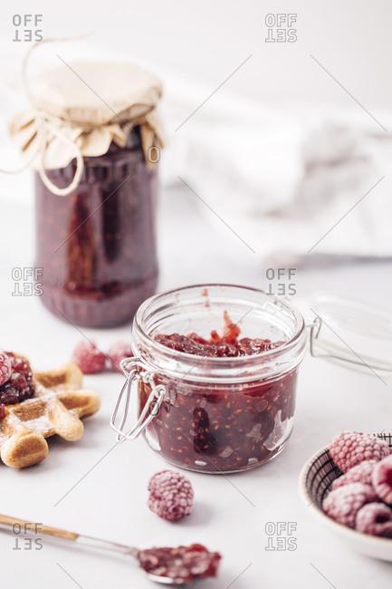 Frozen raspberries in bowl in front of a jar of homemade raspberry jam