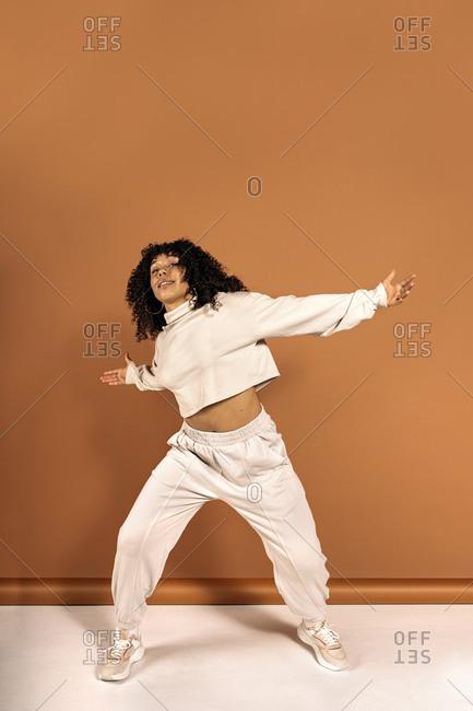 Beautiful African woman with curly hair dancing in studio shot