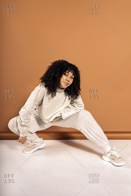 Female African American dancer posing in studio shot against brown background