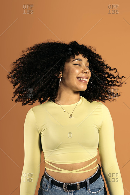 Beautiful African woman moving her curly hair in studio shot