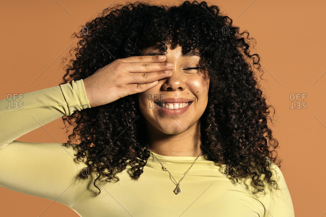 Beautiful African woman with curly hair smiling and covering one eye with her hand in studio shot