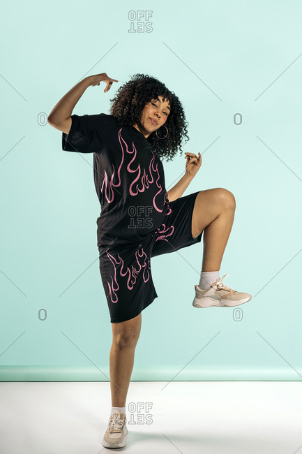 Happy young African woman wearing modern clothes posing in studio shot
