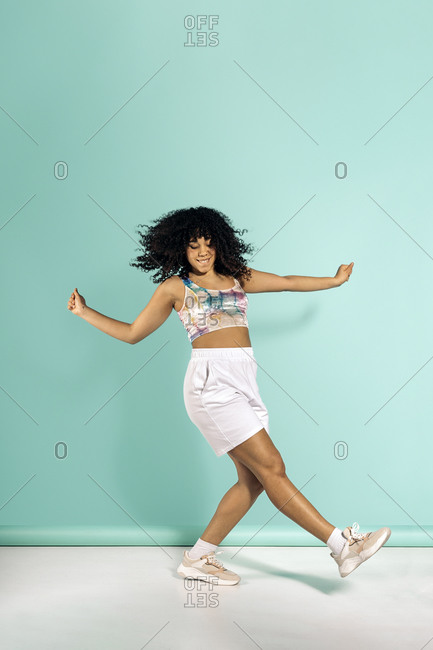Beautiful african woman with curly hair dancing in studio shot against blue background.