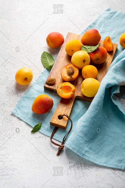 Overhead view of apricots on cutting board and blue linen