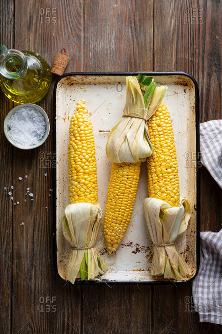Overhead view of Corn cob on baking tray on rustic table
