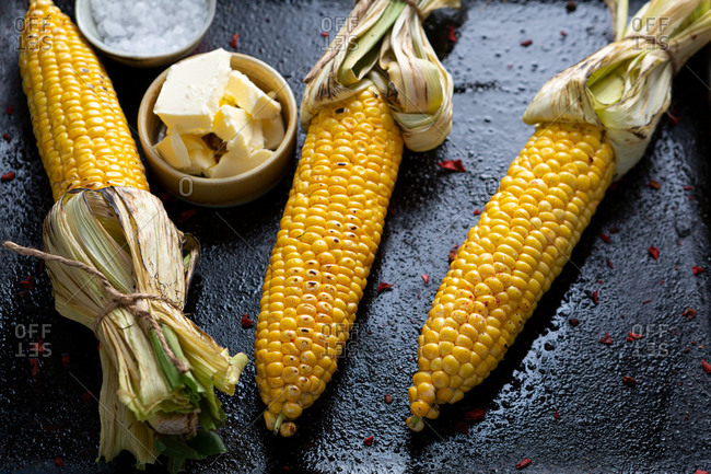 Corn cob with butter and salt on black surface