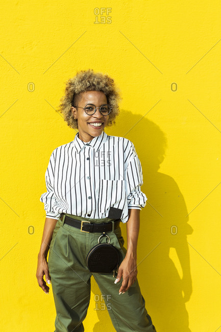 Portrait of a curly haired woman standing in front of a yellow wall