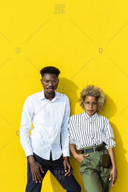 Two friends leaning on a yellow wall while looking at camera