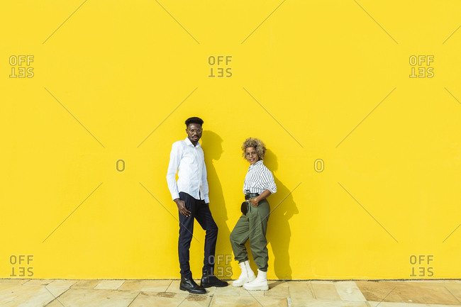 Two people standing in front of yellow wall while looking at camera. Copy space.