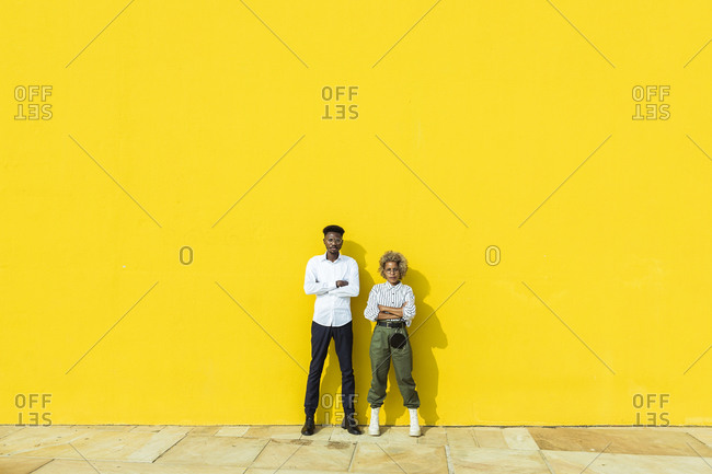 Portrait of a two friends standing together with crossed arms on yellow background. an and a latin woman looking at the camera and crossing arms while standing with a yellow wall on background.