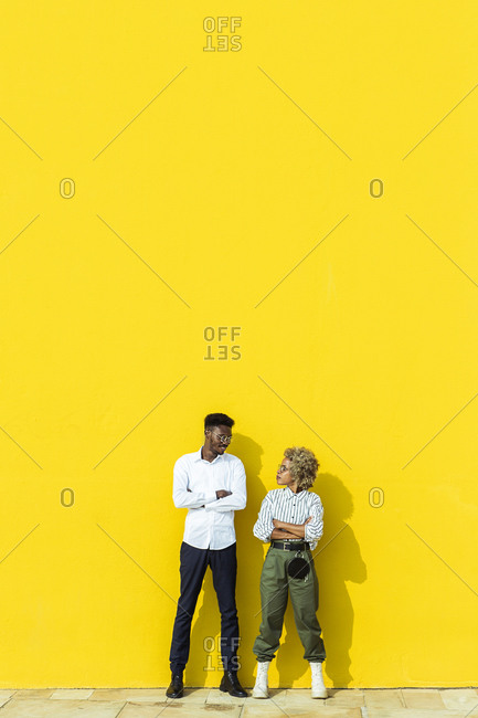 Two friends standing together with crossed arms against yellow background.