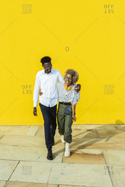 Portrait of an african man and a latin woman embracing each other and smiling while standing with a yellow wall on background.