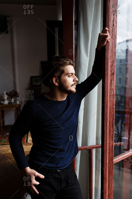 Young man with a beard and beautiful hair at home alone