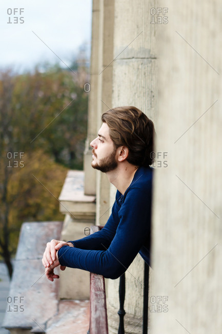 Young man with a beard and beautiful hair on the balcony alone
