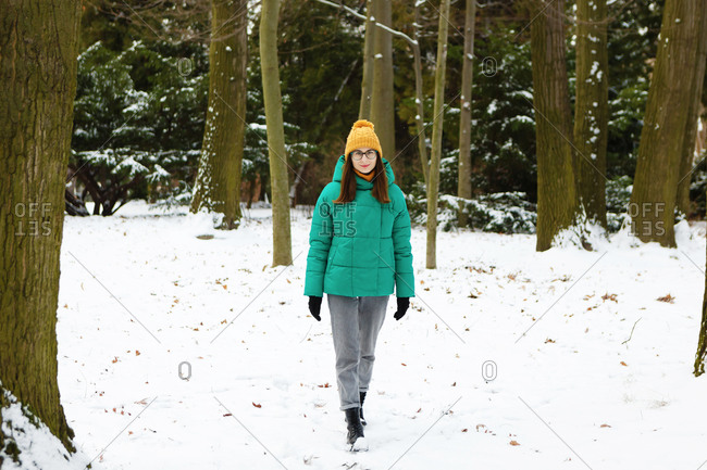 The young female woman in a green winter jacket is walking between the snowy trees in the park or forest that is full of snow