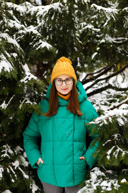 The young female woman in a green winter jacket is standing and touching the snowy trees in the park or forest that is full of snow