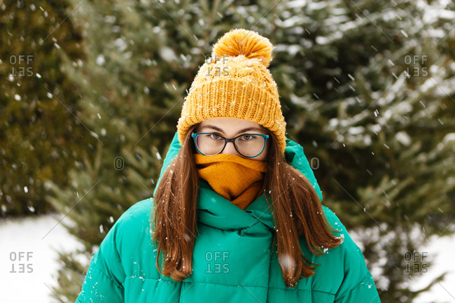 The young female woman is hiding her face  in a scarf because of cold and frost in the park or forest that is full of snow