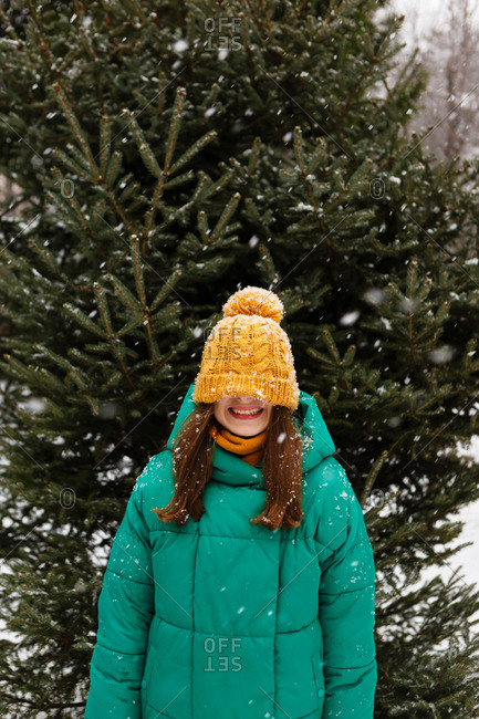 The young female woman is hiding her face in the hat and is laughing because of joy in the park or forest that is full of snow