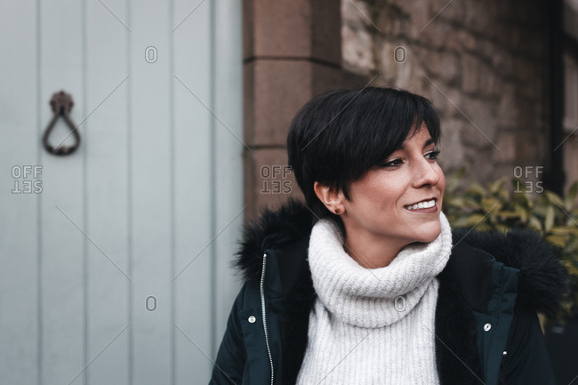 Cheerful woman with short hair wearing winter clothes and smiling in front of her house