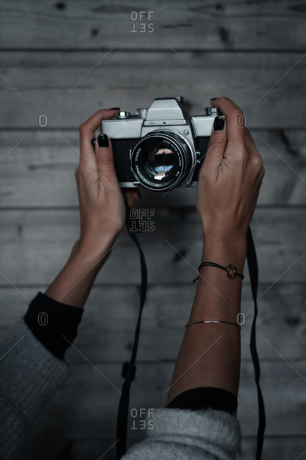 Raising hands of a woman taking a selfie with a film camera towards a wooden wall