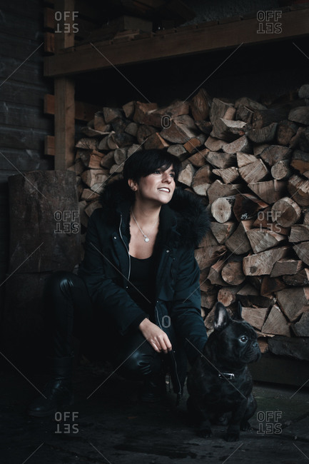 Fashionable woman smiling and bending over in front of a pile of wood chunks with her french bulldog