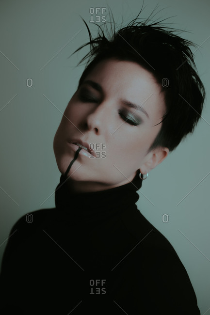 Portrait of an attractive woman with dark makeup and her eyes closed in studio