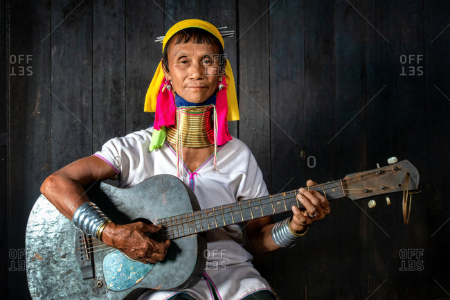PADUANG PEOPLE, PAN PET VILLAGE, KAYAH STATE, MYANMAR - 24 January 2017: Portrait of local lady wearing brass coils placed around the neck, appearing to lengthen  it, while playing a guitar