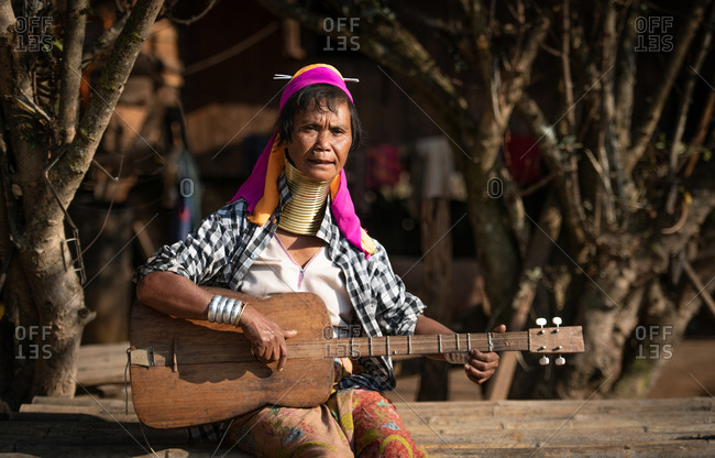 PADUANG PEOPLE, PAN PET VILLAGE, KAYAH STATE, MYANMAR - 28 January 2019: Portrait of local lady wearing brass coils placed around the neck, appearing to lengthen it while playing a guitar