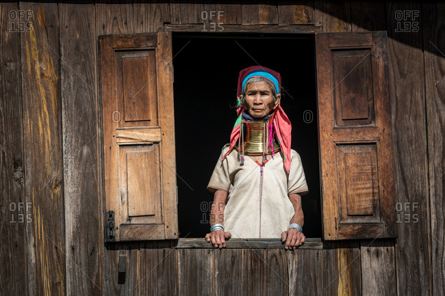 PADUANG PEOPLE, PAN PET VILLAGE, KAYAH STATE, MYANMAR - 20 January 2020: Portrait of Kayan mother and child wearing brass coils placed around the neck, appearing to lengthen it, standing in window.