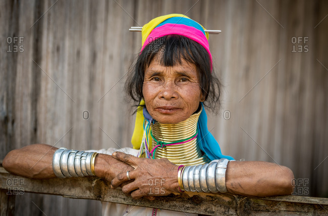 PADUANG PEOPLE, PAN PET VILLAGE, KAYAH STATE, MYANMAR - 28 January 2019: Portrait of local lady wearing brass coils placed around the neck, appearing to lengthen it, leaning on garden fence.