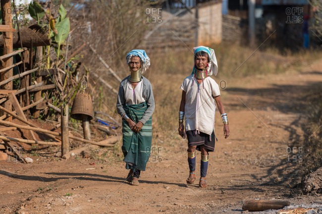 PADUANG PEOPLE,  HILL TRIBE, PAN PET VILLAGE, KAYAH STATE, MYANMAR - 28 January 2019: Grandma and mother walking through village, wearing brass coils placed around the neck, appearing to lengthen it.