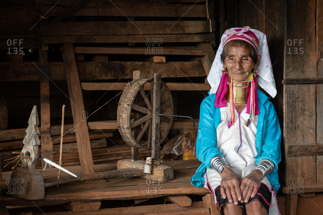 PADUANG PEOPLE,  HILL TRIBE, PAN PET VILLAGE, KAYAH STATE, MYANMAR - 28 January 2019: Portrait of local lady wearing brass coils placed around the neck, appearing to lengthen it, with spinning wheel.